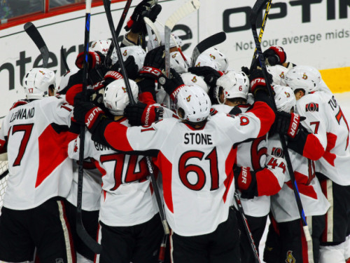 Ottawa Senators players celebrate after clinching a playoff spot with a win against the Philadelphia Flyers in the final game of the 2014/15 season. (AP Photo/Tom Mihalek)