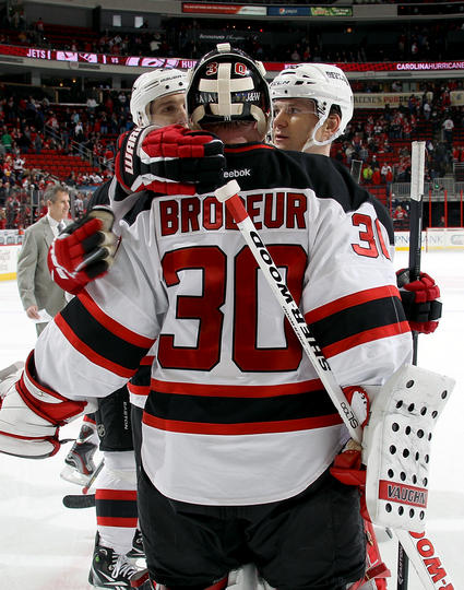 Teammates surround Martin Brodeur #30 of the New Jersey Devils